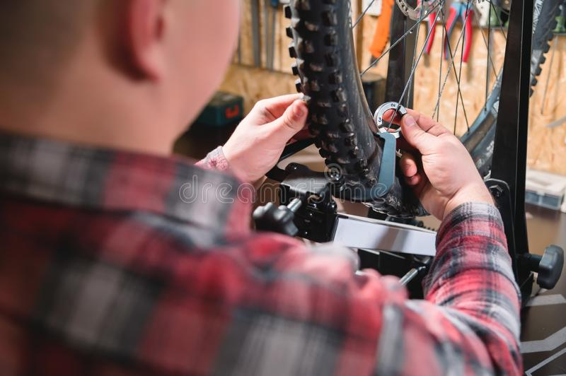 Young male bicycle repairman with a specialized wrench on a stand in the workshop, tightening the spokes of the wheel royalty free stock photo