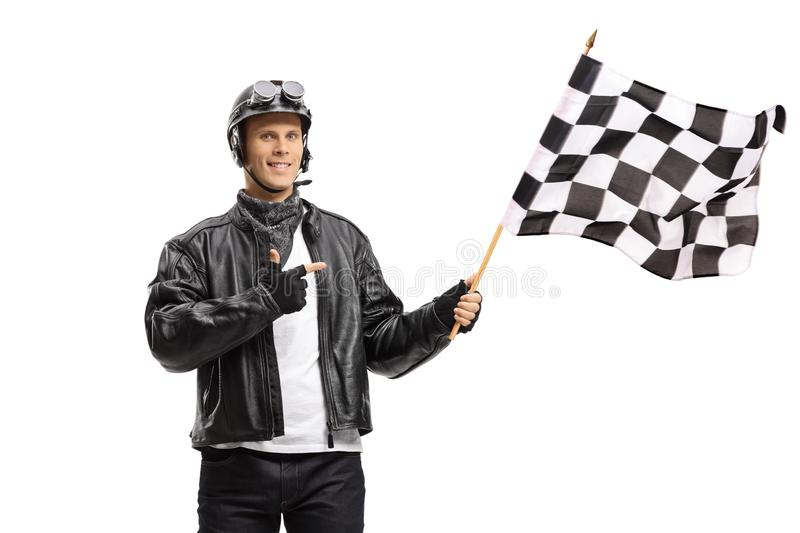 Young male biker waving a checkered race flag and pointing royalty free stock images