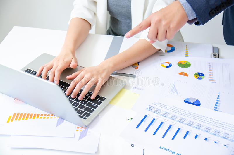 Young male boss commanding his young beautiful worker in work table with graph and chart on office desk stock images