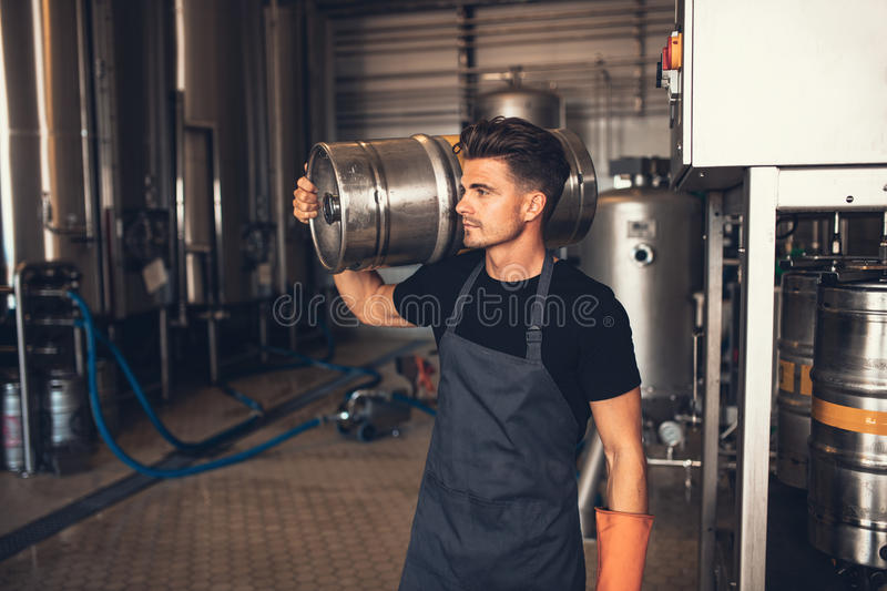 Young male brewer carrying keg at brewery. Manual worker with metal beer barrel craft beer manufacturing plant stock image