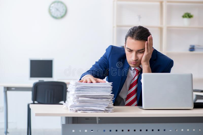 Young male businessman sitting in the office royalty free stock image