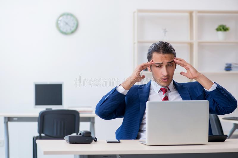 Young male businessman sitting in the office. The young male businessman sitting in the office royalty free stock image