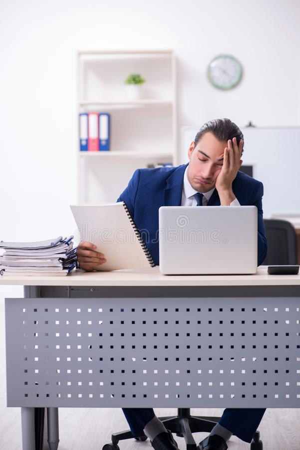 Young male businessman working in the office. The young male businessman working in the office stock image