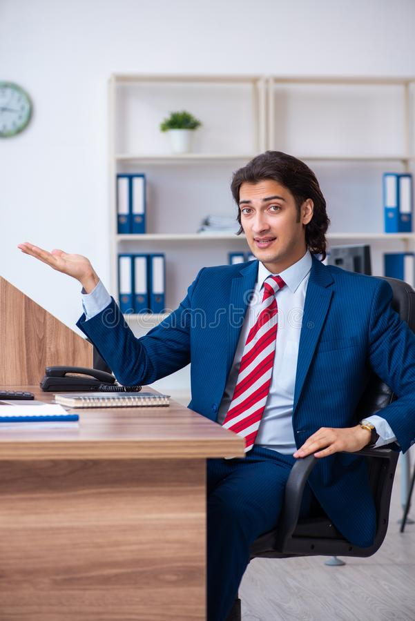 Young male businessman working in the office. The young male businessman working in the office stock photography