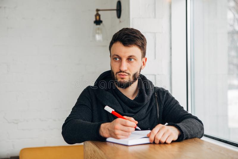Young male businessman writing on a notepad on wood desk in coffee cafe shop royalty free stock photography