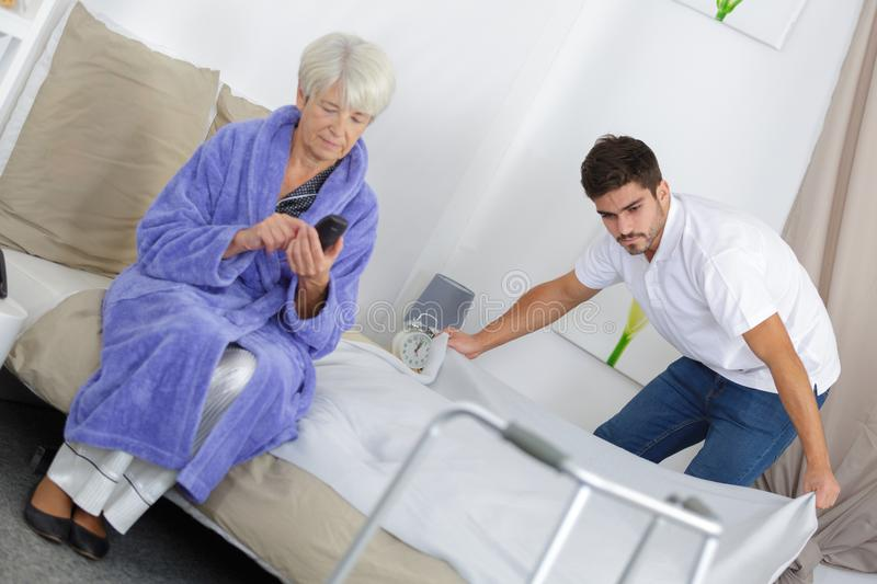 Young male carer spending time with elderly woman stock images