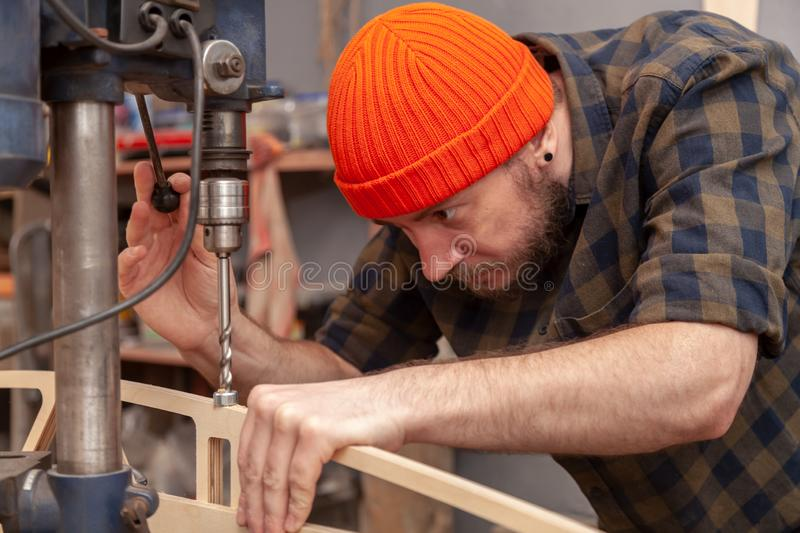 A young male carpenter builder. Carpenter man in work clothes drills a hole in wooden product with an electrical drill.Concept of do-it-yourself male work with stock images