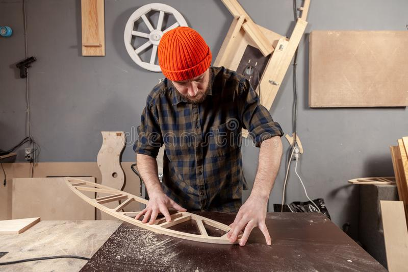 A young male carpenter builder. In a  working clothes equals a wooden bar with a milling machine in the workshop, in the background wooden boards royalty free stock photography