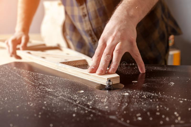 A young male carpenter builder. In a  working clothes equals a wooden bar with a milling machine in the workshop, in the background wooden boards royalty free stock images