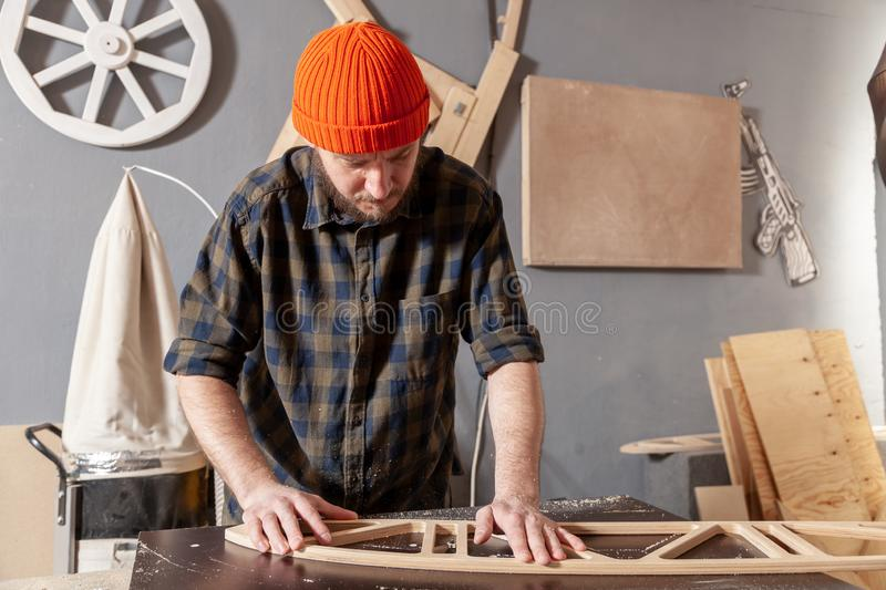 A young male carpenter builder. In a  working clothes equals a wooden bar with a milling machine in the workshop, in the background wooden boards royalty free stock photos