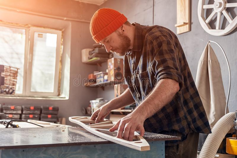 A young male carpenter builder. A young man carpenter builder in work clothes processing a wooden board with a milling machine in the workshop, around a lot of stock image