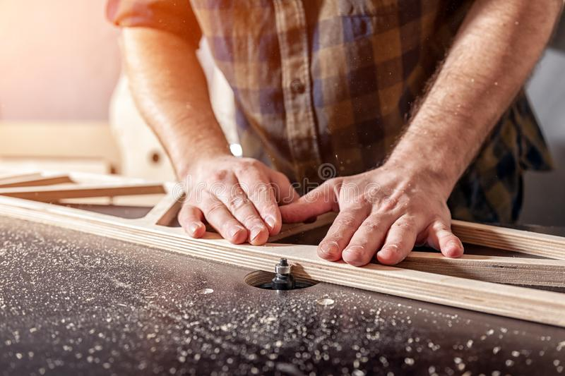 A young male carpenter builder. A young man carpenter builder in work clothes processing a wooden board with a milling machine in the workshop, around a lot of royalty free stock photo