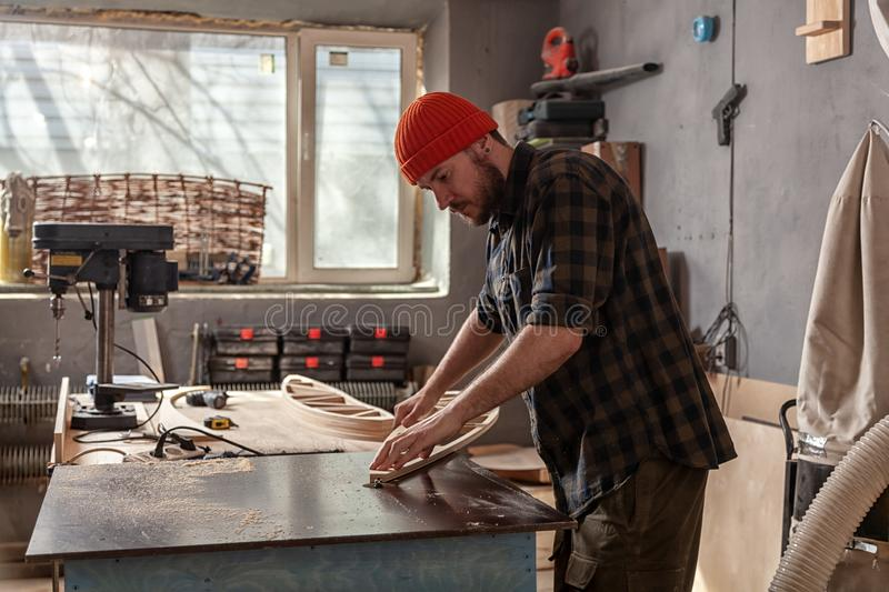 A young male carpenter builder. A young man carpenter builder in work clothes processing a wooden board with a milling machine in the workshop, around a lot of royalty free stock photos