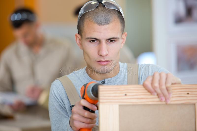 Young male carpenter making wooden frame royalty free stock image