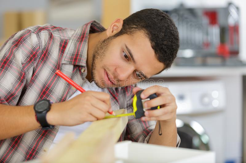 Young male carpenter measuring wood royalty free stock photos