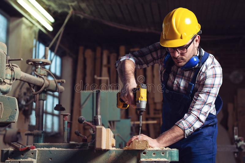 Male carpenter using drill to repair a chair in a workshop royalty free stock images