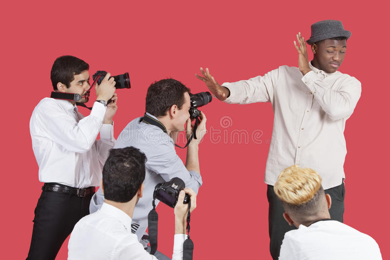 Young Male Celebrity Shielding Face From Photographers Over Red Background Royalty Free Stock Photography
