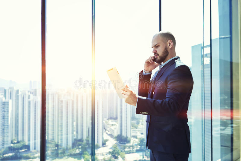 Young male CEO having serious mobile phone conversation. Confident man successful entrepreneur dressed in suit is reading the monthly report on portable digital royalty free stock image