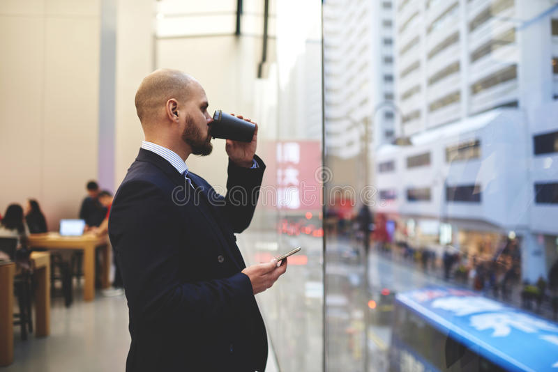 Young male CEO is resting after work day. Thoughtful man professional banker with mobile phone in hand is drinking take away coffee while standing near big stock photo