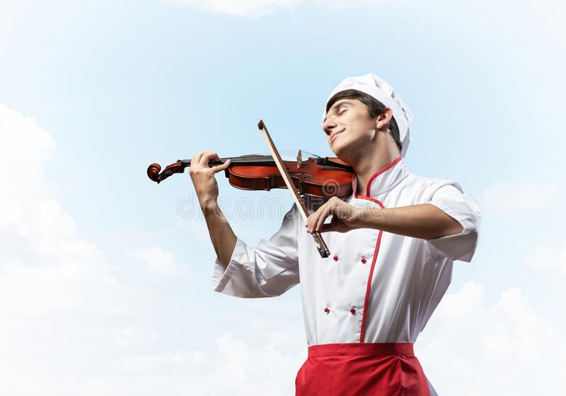 Young male chef playing violin royalty free stock photos