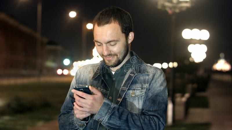 Young male in the city using his smartphone. royalty free stock photos