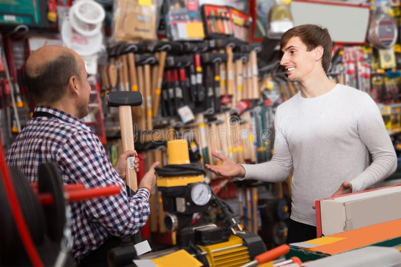 Young male client and mature salesman at tooling section stock image