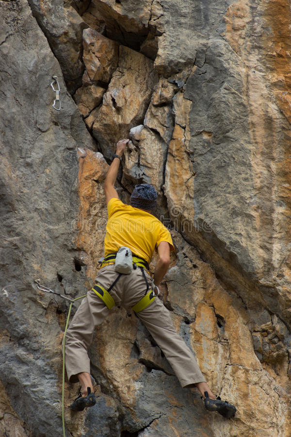Young male climber hanging by a cliff. Young male climber hanging on a cliff with a rope royalty free stock photos