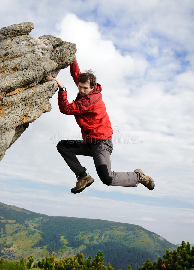 Young male climbing on a cliff royalty free stock image