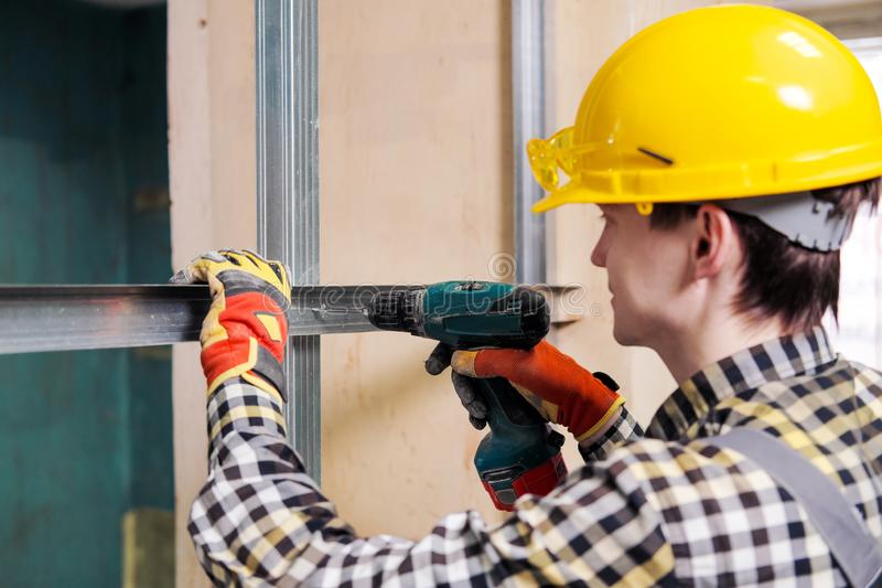 Young male construction worker and repairman working with a screwdriver and metal profile. stock image