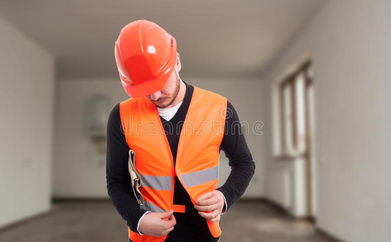 Young male constructor adjusting his protection vest royalty free stock photo