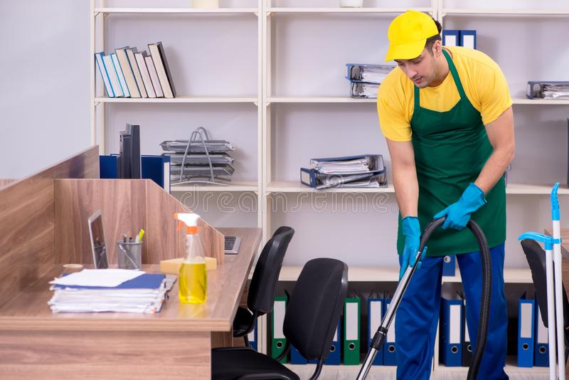 Young male contractor cleaning the office stock images