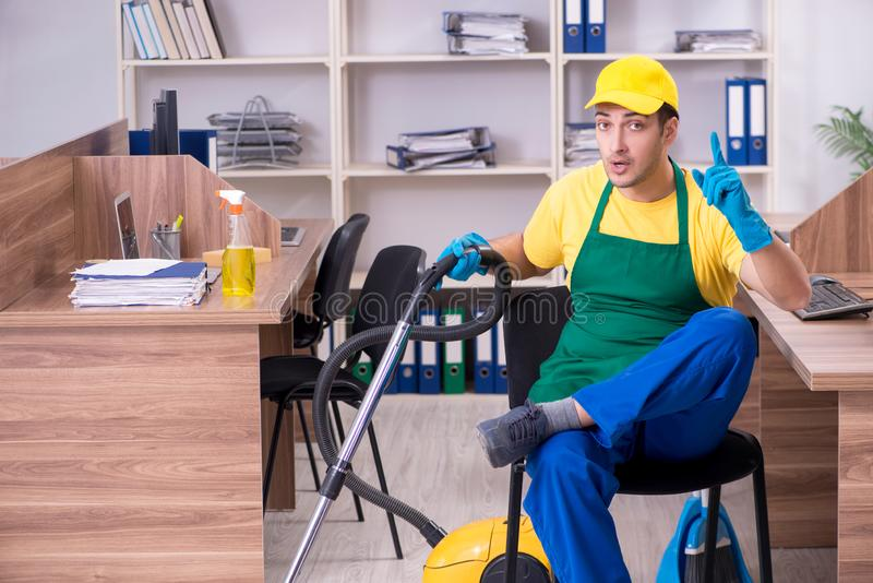 Young male contractor cleaning the office stock photography