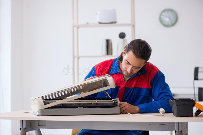 Young male contractor repairing air-conditioner at workshop. The young male contractor repairing air-conditioner at workshop royalty free stock photos