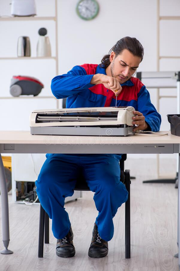 Young male contractor repairing air-conditioner at workshop royalty free stock images