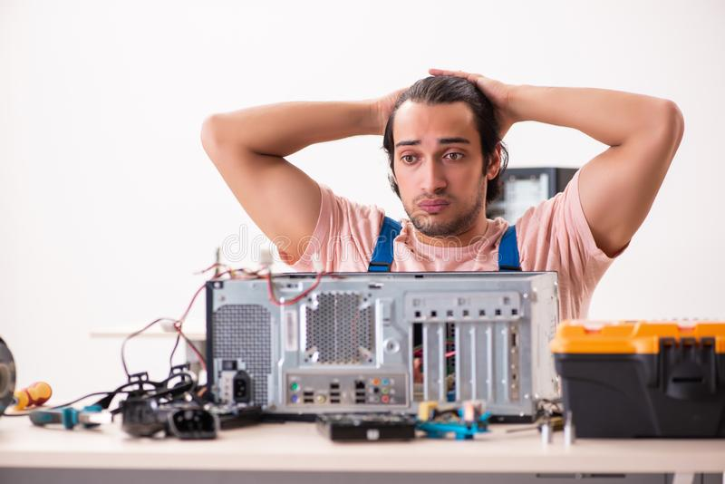 The young male contractor repairing computer stock photography