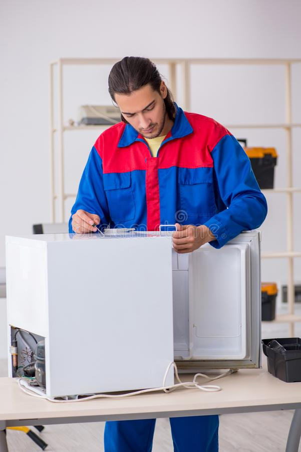 Young male contractor repairing refrigerator at workshop. The young male contractor repairing refrigerator at workshop royalty free stock images