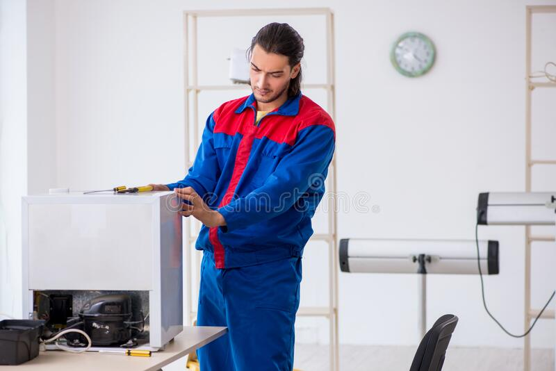 Young male contractor repairing refrigerator at workshop stock image