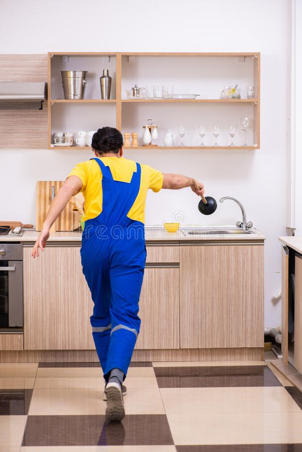 Young male contractor repairing tap at home. The young male contractor repairing tap at home royalty free stock image