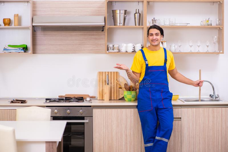 Young male contractor repairing tap at home. The young male contractor repairing tap at home royalty free stock photos