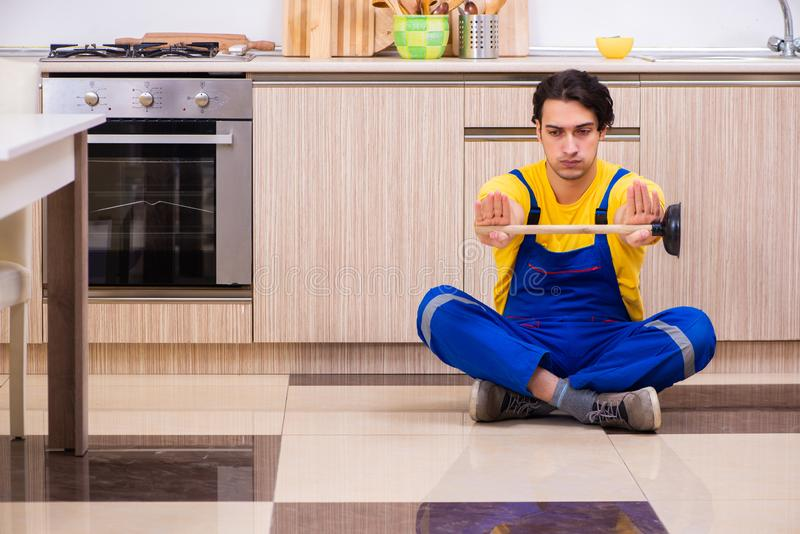 Young male contractor repairing tap at home. The young male contractor repairing tap at home stock photo