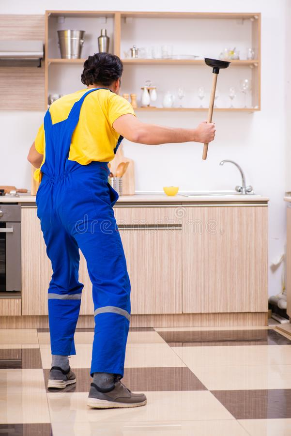 Young male contractor repairing tap at home. The young male contractor repairing tap at home stock photos