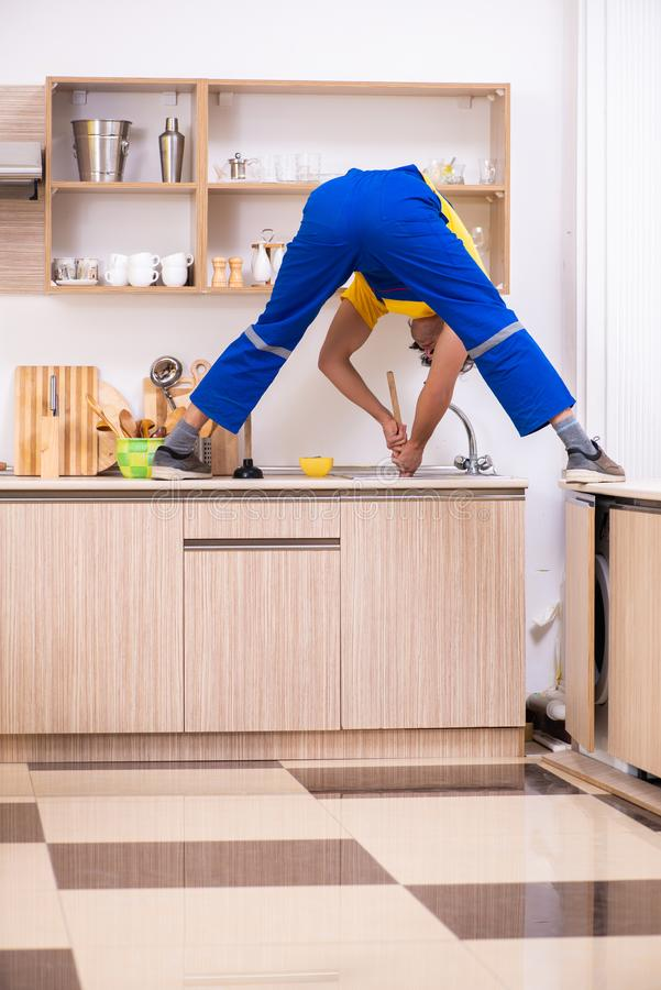Young male contractor repairing tap at home. The young male contractor repairing tap at home royalty free stock images