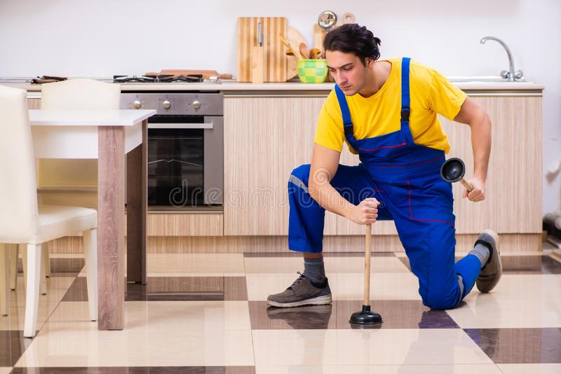 Young male contractor repairing tap at home. The young male contractor repairing tap at home stock photography