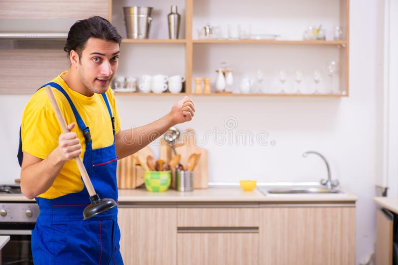 Young male contractor repairing tap at home. The young male contractor repairing tap at home stock image