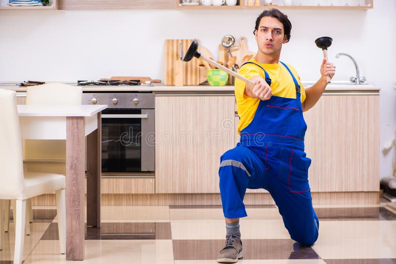 Young male contractor repairing tap at home. The young male contractor repairing tap at home stock images