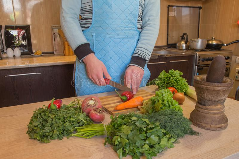 Young Male cooking healthy meal in the kitchen. Cooking healthy food at home. Man in kitchen preparing vegetables. Chef cuts the v. Egetables into a meal stock images