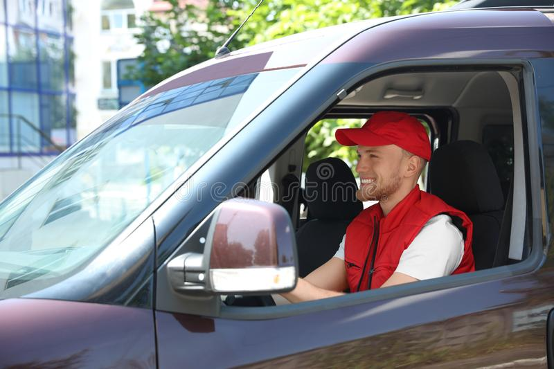 Young male courier in delivery van stock images