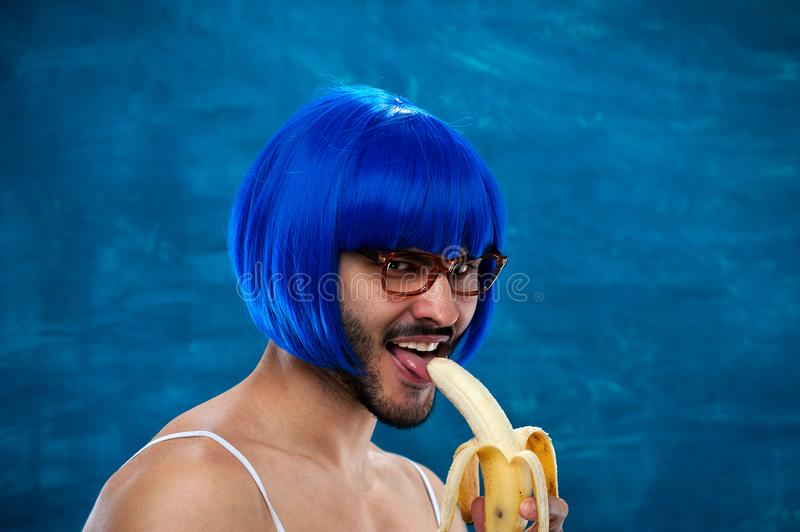Young male cross dressing person wearing blue wig. Sensual young male cross dressing person wearing blue wig and female cloth eats banana. Place for text stock images