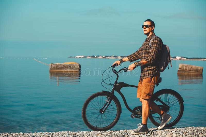 Young Male Cyclist With Bicycle Walking On Coast And Enjoying View Of Sea. Holiday Travel Activity Concept royalty free stock photos