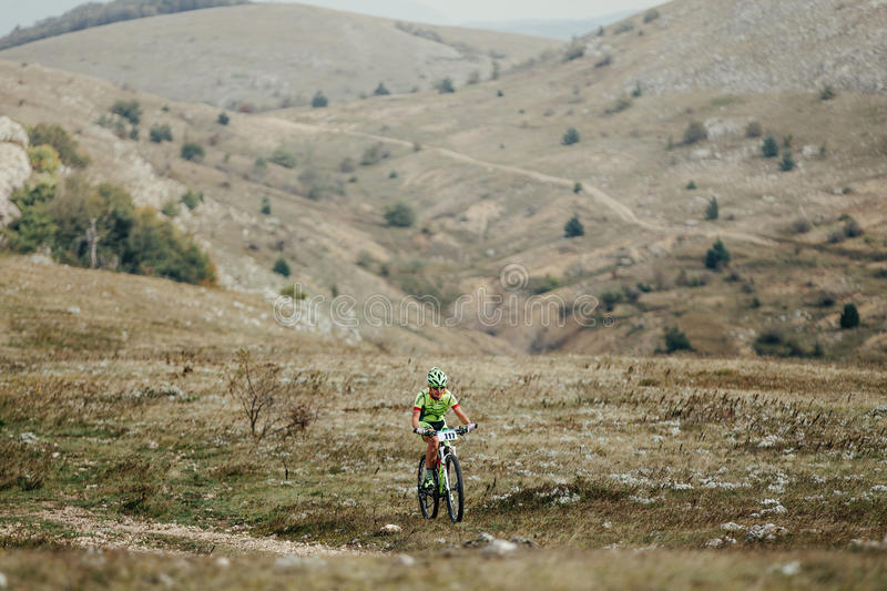 Young male cyclist mountainbiker riding on a mountain valley royalty free stock photography